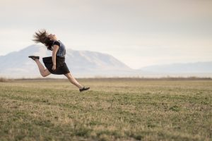 Photo of a girl wearing a black skirt and grey top on a grassy plain jumping for joy.